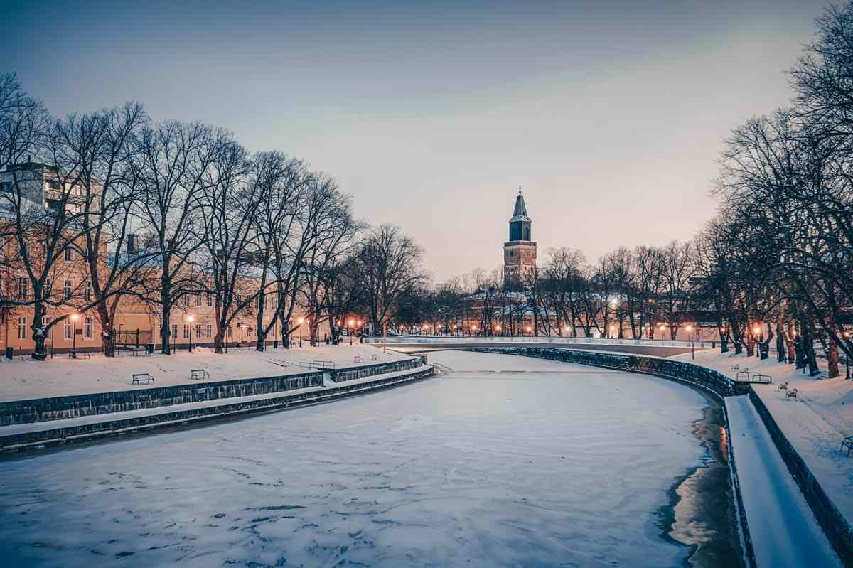 Things to do in Turku: View of the frozen Aura River and Turku Cathedral in winter