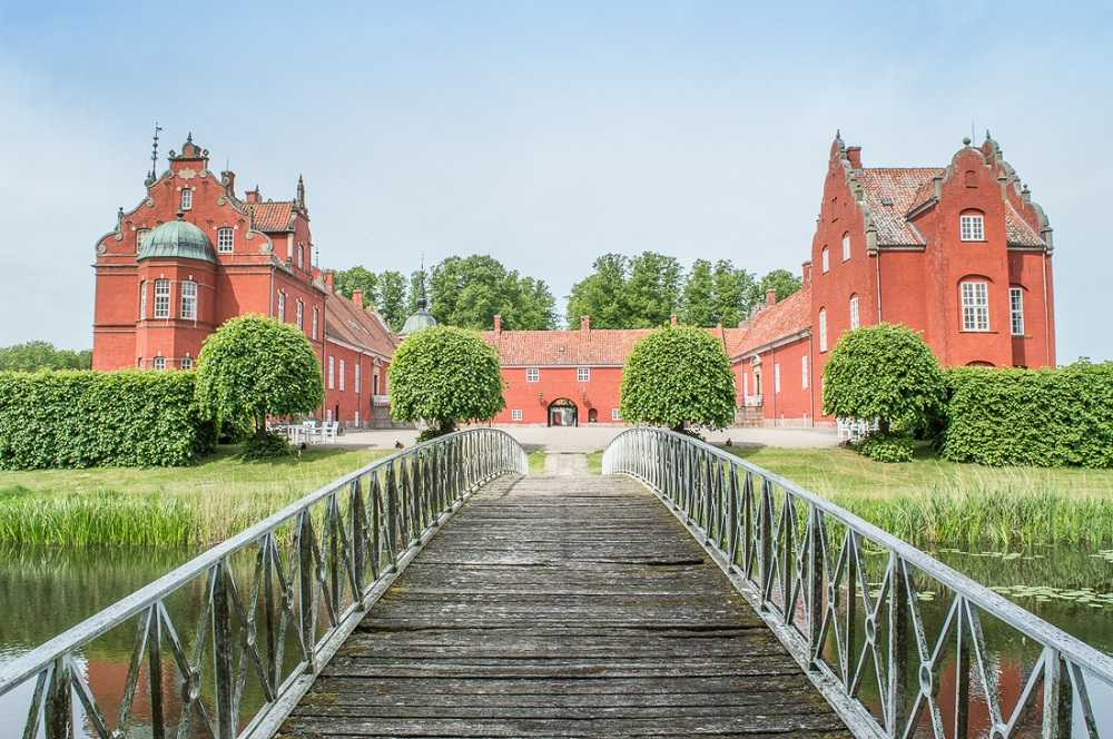 Castles in Sjælland: Photo of a wooden bridge leading to Løvenborg Castle in the background.