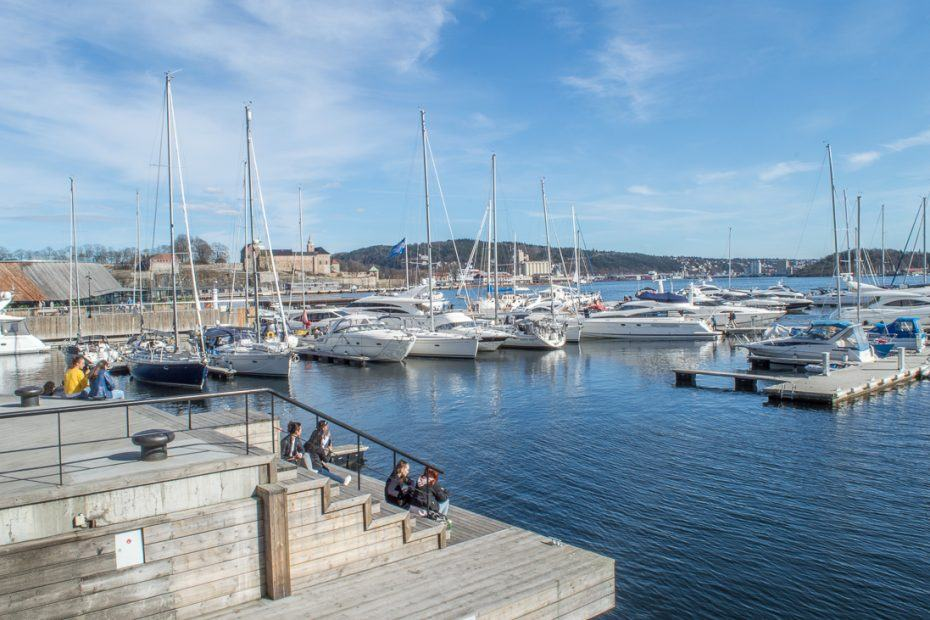One Day in Oslo: This picture shows the marina at Aker Brygge. In the front there is a pier which a few people are sitting upon. In the background there are sailing ships.