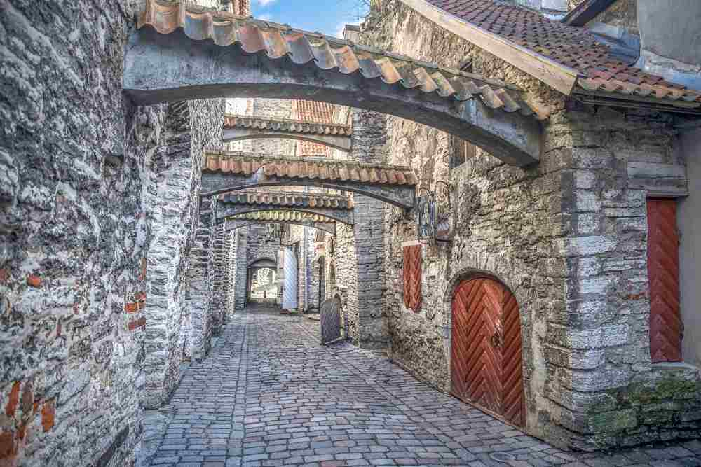 Tallinn walking tour: The St. Catherine's Passageway is an enchanting medieval alleyway with uneven stone walls and overhead vaulting and one of the best things to see in Tallinn.