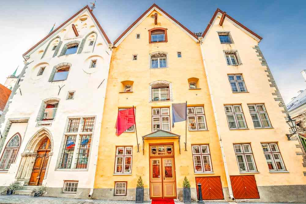 Things to do in Tallinn: The colorful facades of the famous Three Sisters buildings feature loading hatches and winches to hoist sacks of goods up and down. It is one of the must-see attractions on a Tallinn walking tour.