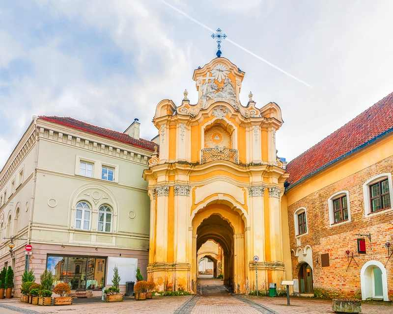 What to do in Vilnius: The famous Basilian Gate is a coffee-and-cream archway that carries a white bas-relief depiction of the Holy Trinity.