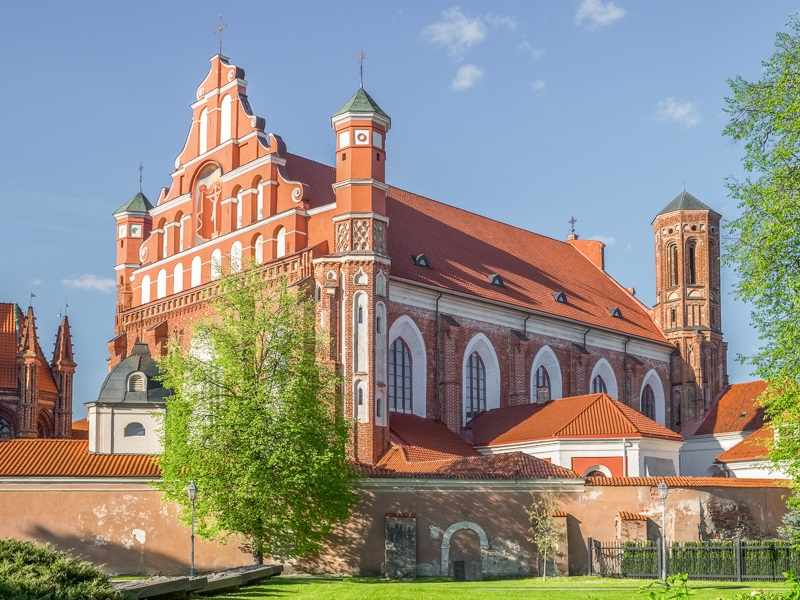 What to see in Vilnius: Exterior of the Bernardine Church which is an interesting blend of Gothic and Baroque styles, making it one of the best places to see on a self-guided walking tour of Vilnius.