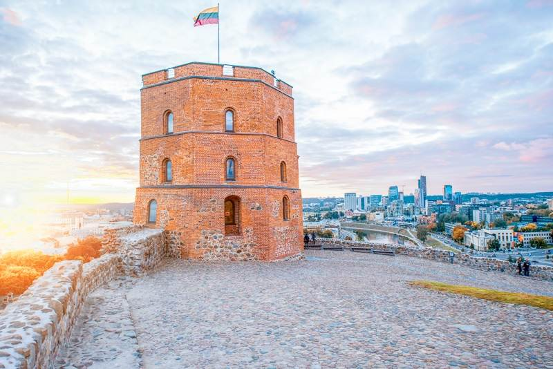 Free Vilnius Self-Guided Walking Tour: View on Gediminas' Tower on the Castle Hill during at sunset. This red-brick tower is one of the must-see attractions in Vilnius.