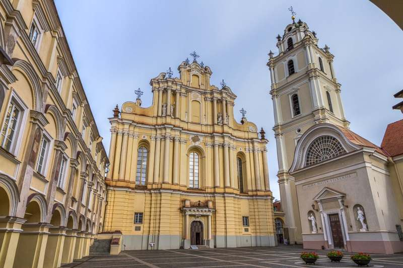 What to see in Vilnius: The Grand Courtyard of the renowned Vilnius University is also home to the custard colored Baroque style Church of St. John.