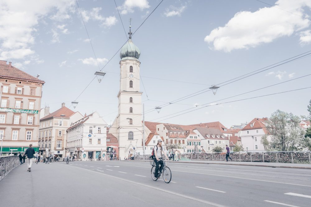 A cyclist crosses a bridge in Graz.