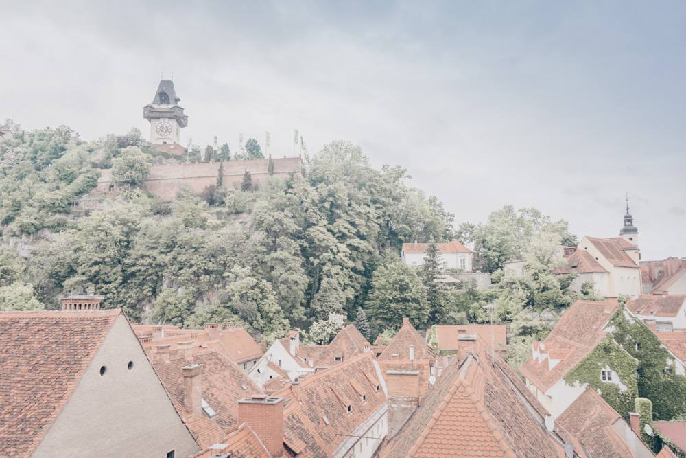 Photo of the Graz clock tower sitting atop the Schlossberg as seen from a rooftop terrace.