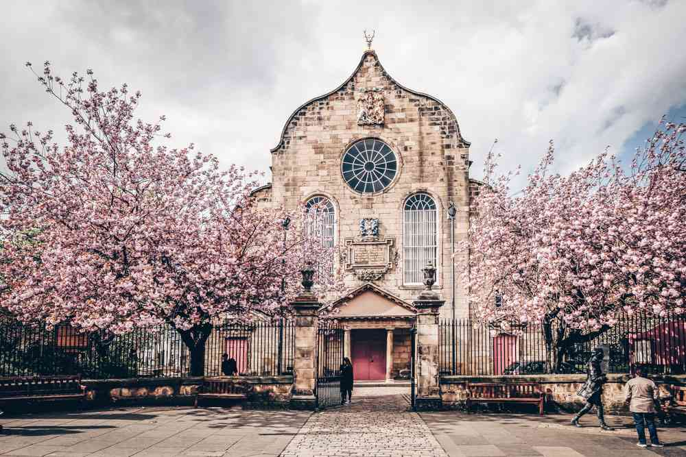 What to do in Edinburgh: View of the Canongate Kirk facade with its gracefully arched facade, round windows, and bow-shaped gable. It is one of the highlights of this Edinburgh walking tour.