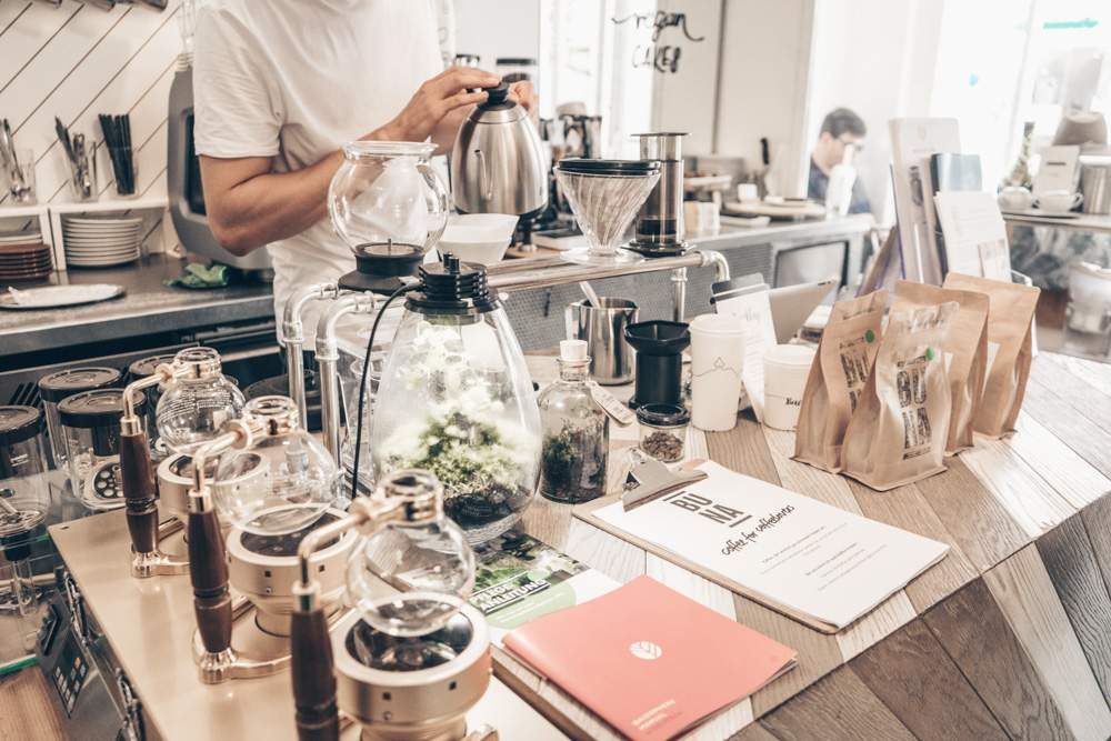 Somebody prepares tea at Buna Kaffee in Graz while various gadgets and bags of coffee stand in the foreground.