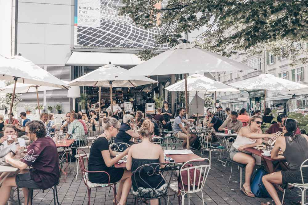 Several groups of people enjoying coffee and food on a sunny day, shaded by large parasols, just outside the Kunsthaus Cafe.