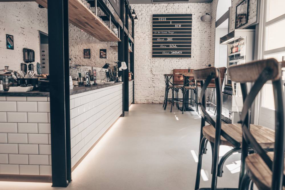 So/So Cafe in Graz features high tables and chairs paired against a clean background of concrete floors and white brick walls.