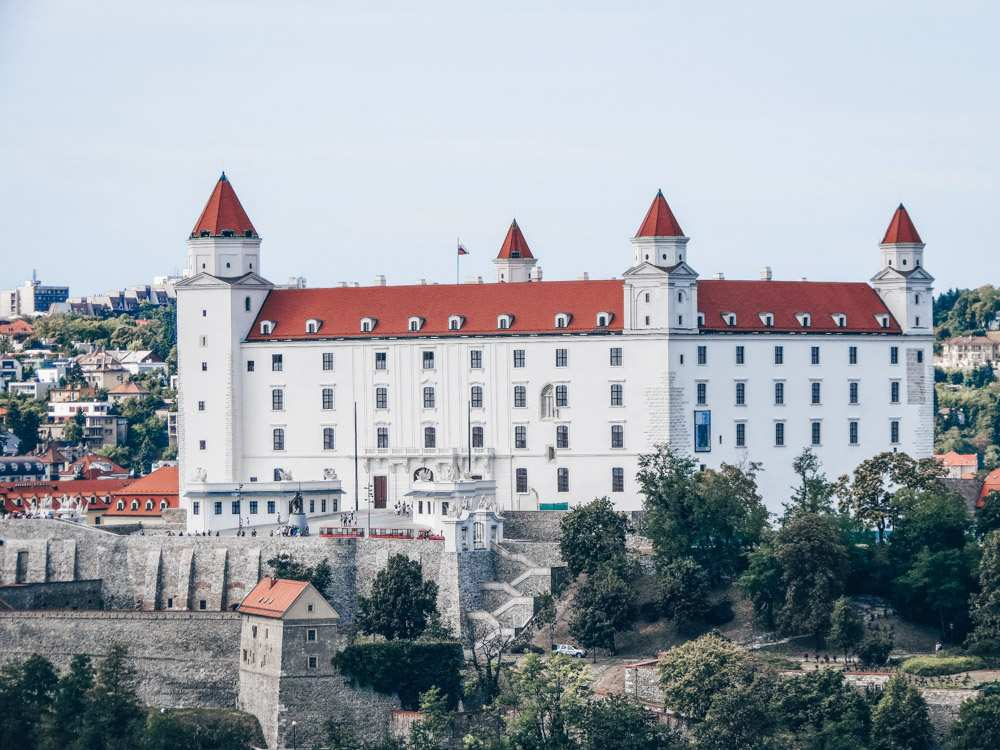 Free Bratislava walking tour: View of the four towers of the strikingly white, rectangular Bratislava Castle, one of the must-see attractions in Bratislava.