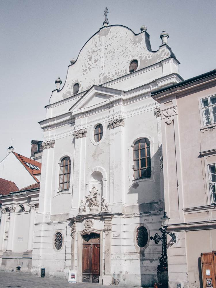 Bratislava Churches: View of the slightly outworn and inconspicuous Baroque facade of the Franciscan Church, the oldest church in Bratislava. PC: Lure [CC BY-SA 3.0 (https://creativecommons.org/licenses/by-sa/3.0)], via Wikimedia Commons.