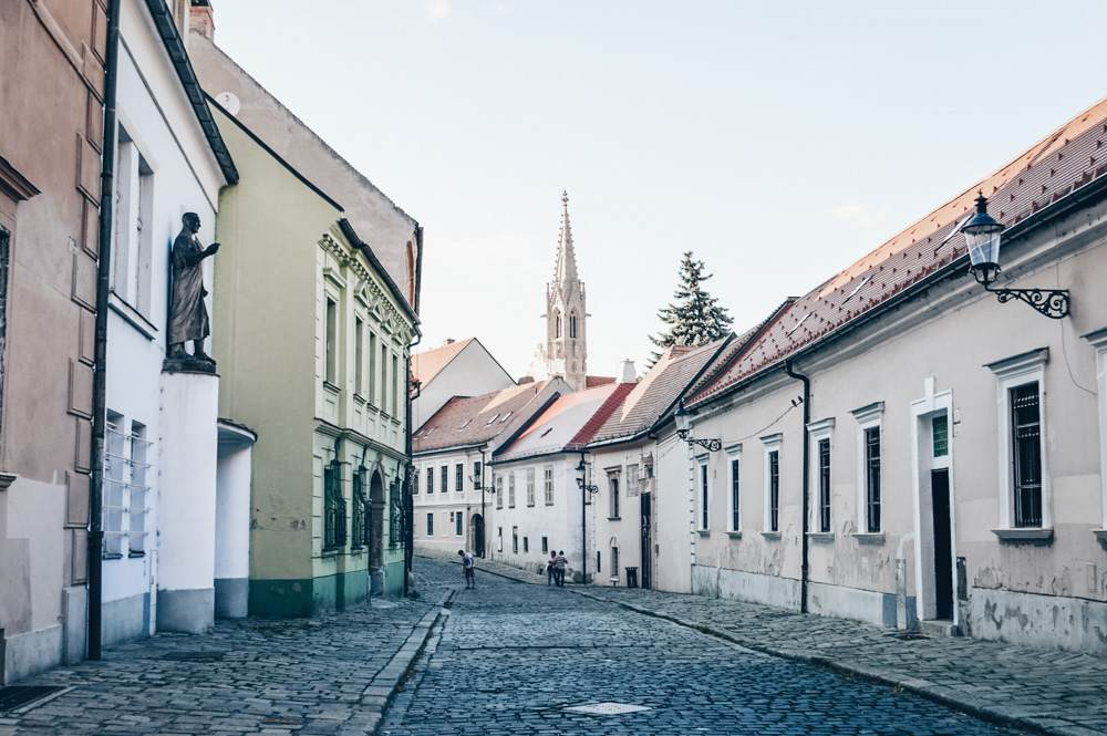 Things to do in Bratislava: Kapitulska Street, a postcard-perfect little alley dating back to the 14th century is one of the must-see places when exploring Bratislava on foot. PC: Francisco Anzola [CC BY 3.0 (https://creativecommons.org/licenses/by/3.0)], via Wikimedia Commons.