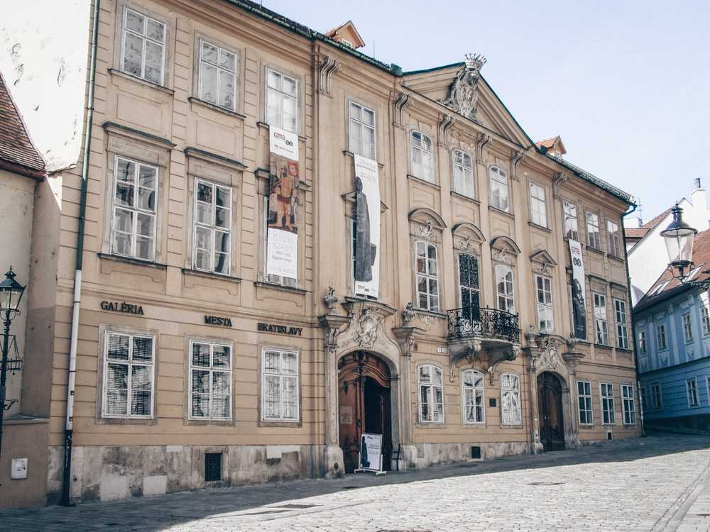 What to see in Bratislava: View of the four-winged two-story Mirbach Palace with saddle roofs and triangular pediment. It is one of the best palaces in Bratislava. PC: Lure [CC BY-SA 3.0 (https://creativecommons.org/licenses/by-sa/3.0)], via Wikimedia Commons.