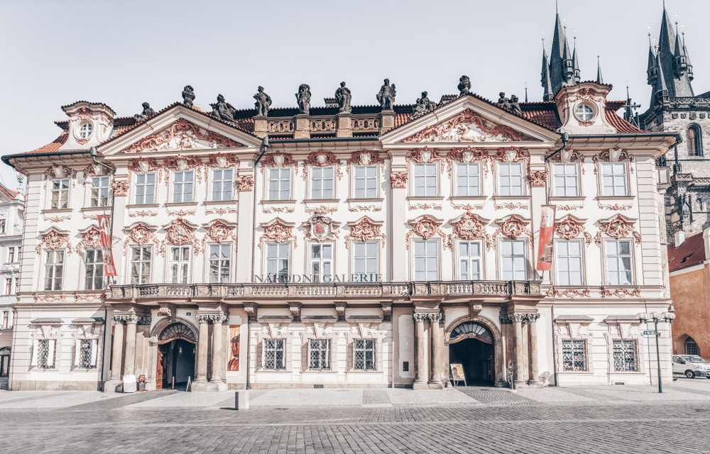 Best palaces in Prague: View of the gorgeous pink and white stuccoed Rococo facade of the Kinsky Palace. It is one of the highlights of this free Prague walking tour.
