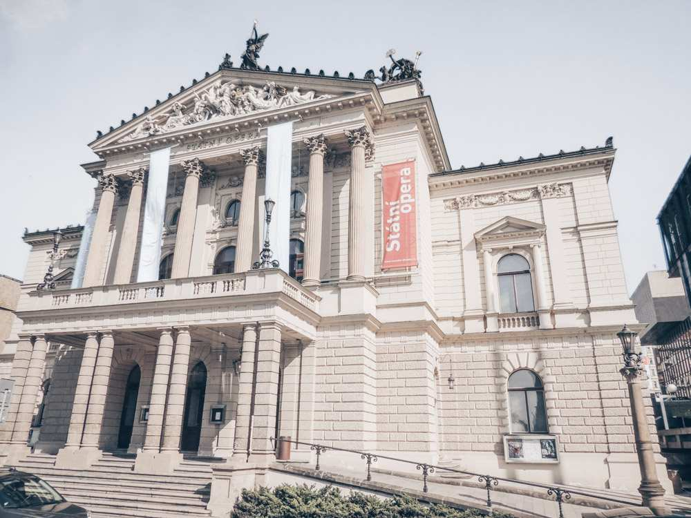 Free self-guided Prague walking tour: View of the Neoclassical facade of the State Opera, the leading Opera house and one of the best places to visit in Prague.