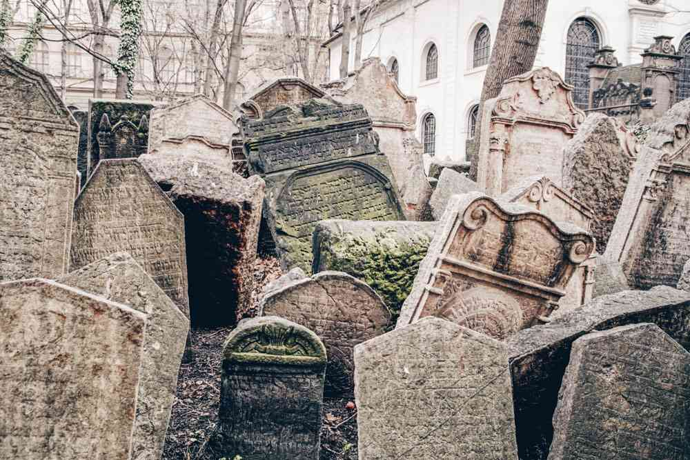 Must-see sights in Prague: View of the lopsided tombstones in the Old-Jewish cemetery, one of the best things to see in the Prague Jewish Quarter.