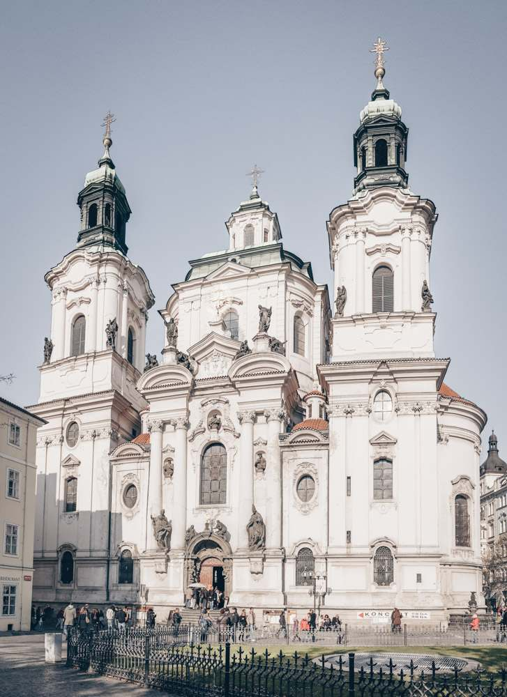 Best churches in Prague: View of the dramatic white facade of the Church of St. Nicholas that is studded with statues. It is one of the best things to see when exploring the Old Town Square in Prague. PC: Petr Šmerkl [CC BY-SA 3.0 (https://creativecommons.org/licenses/by-sa/3.0)], via Wikimedia Commons.