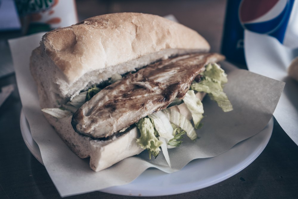 Istanbul Balik Ekmek - Grilled fish with raw onions and lettuce sandwiched in a bread.