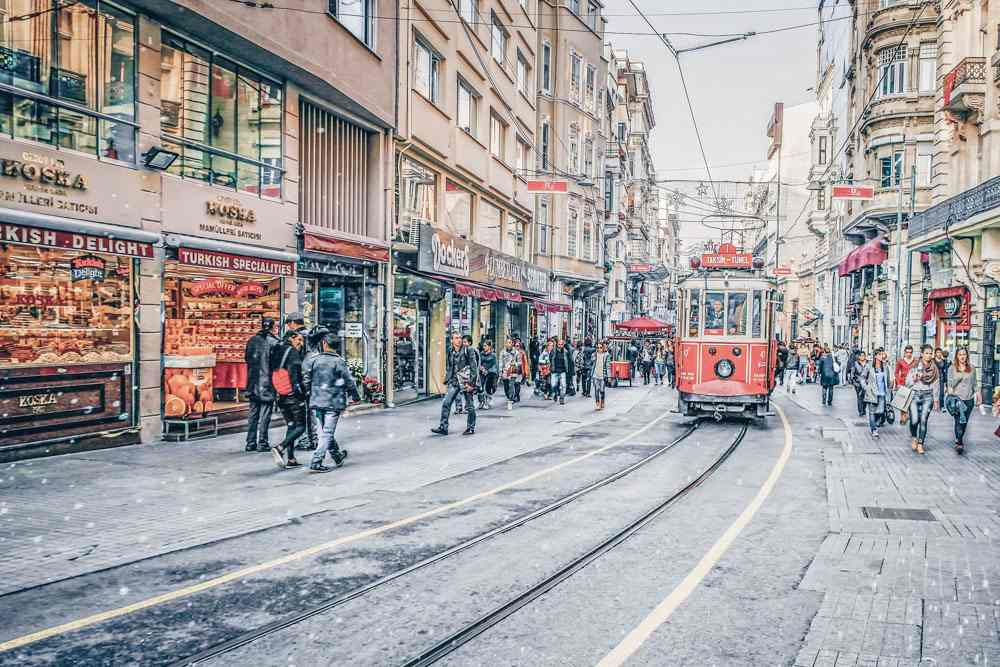 Things to do in Istanbul - Red vintage tram and people on Istiklal Street. PC: Perekotypole/shutterstock.com
