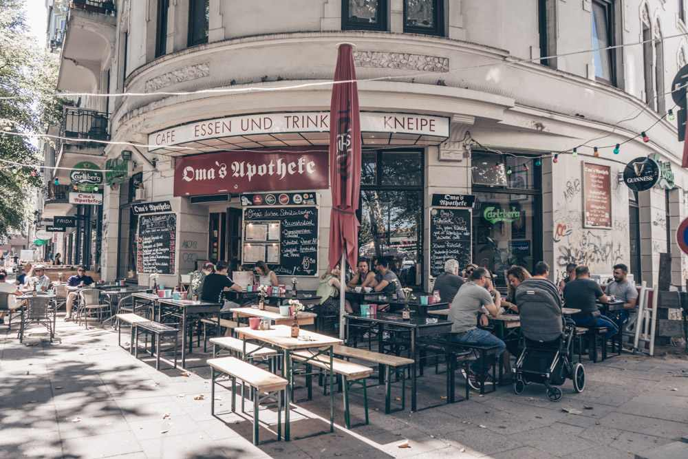 Things to do in Hamburg - People sitting on benches outside a cafe in the Sternschanze Quarter,