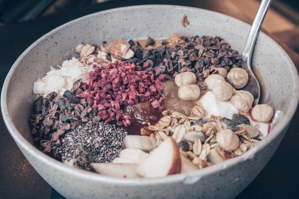Where to eat in Copenhagen: A bowl of porridge consisting of chia seeds, cocoa nibs, apples, and bananas at GRØD