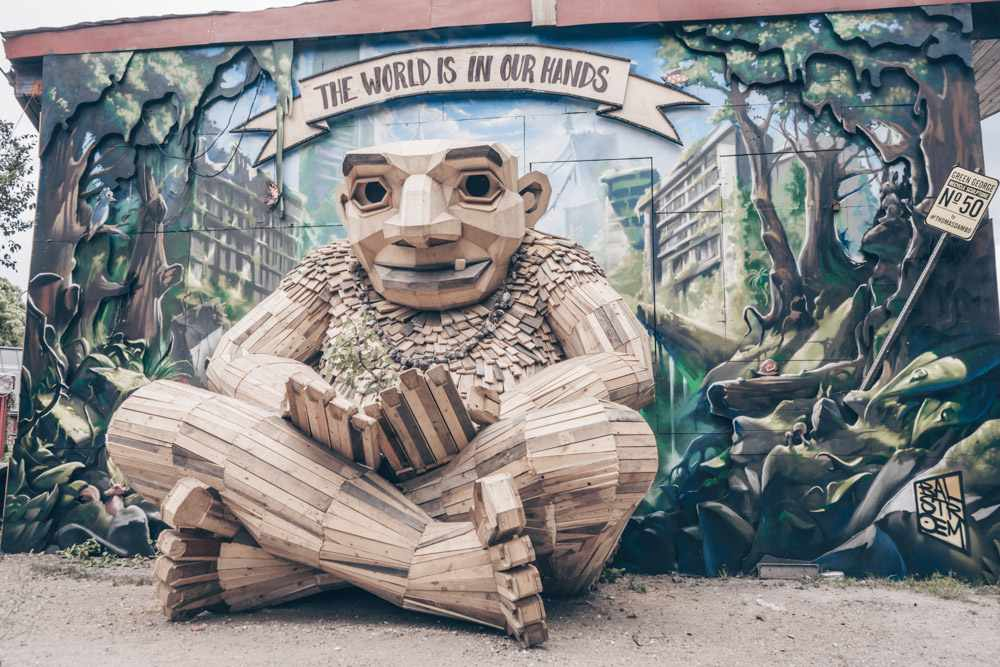 Copenhagen Christiania: Carved wooden sculpture in front of a mural
