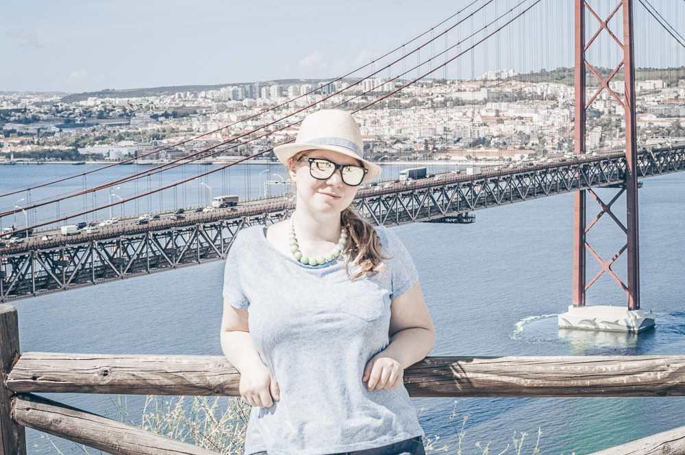 3 Days in Lisbon: Picture of a pretty woman with the 25 de Abril Bridge in the background.