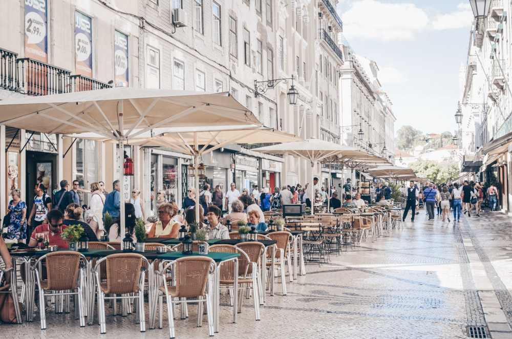 Lisbon sightseeing: People sitting in outdoor cafes on Rua Augusta.