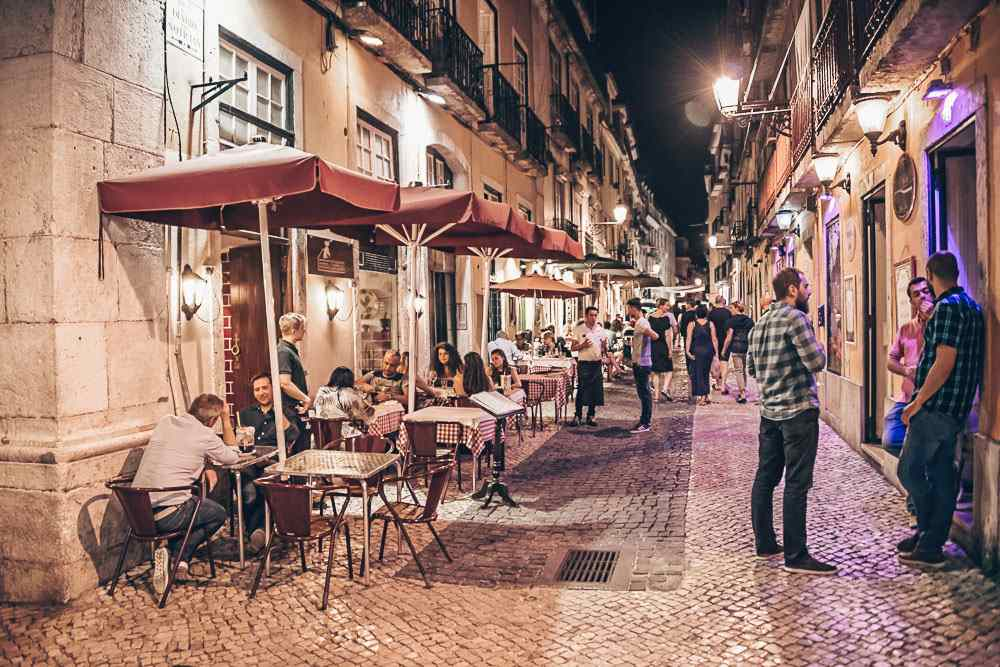 Lisbon Neighborhoods: People in a small alley in the Bairro Alto at night. PC: Salvador Aznar/shutterstock.com