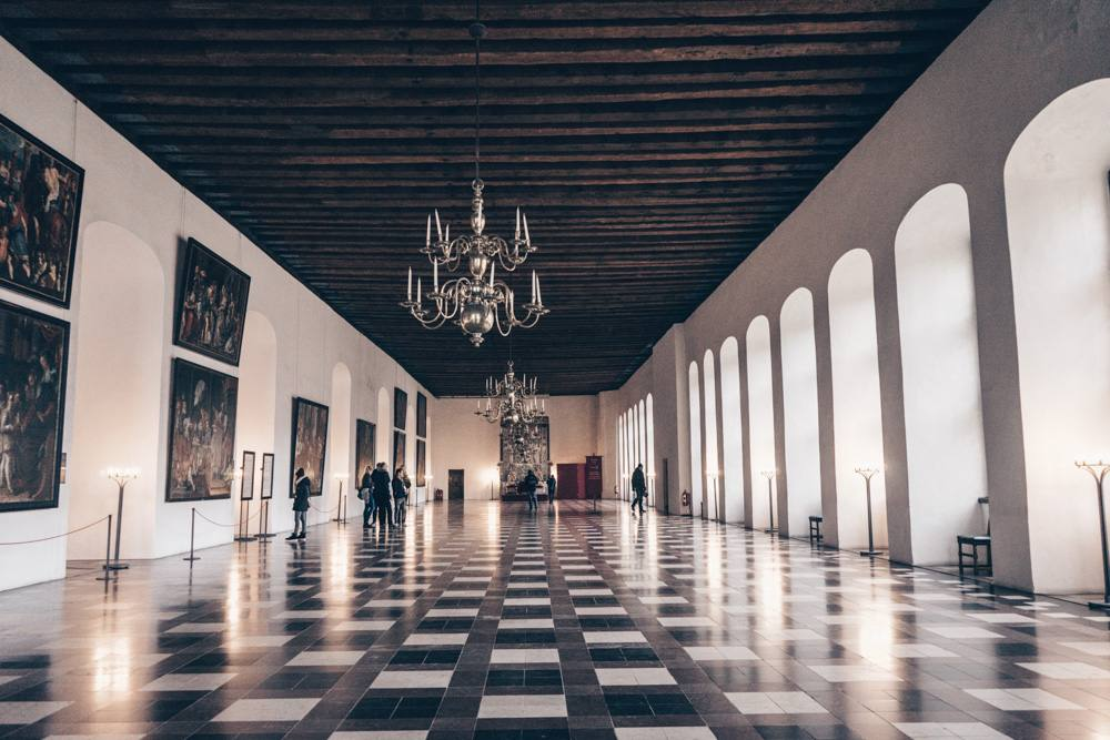 Kronborg Castle: People admiring the portraits in the sprawling Ballroom of Kronborg Castle