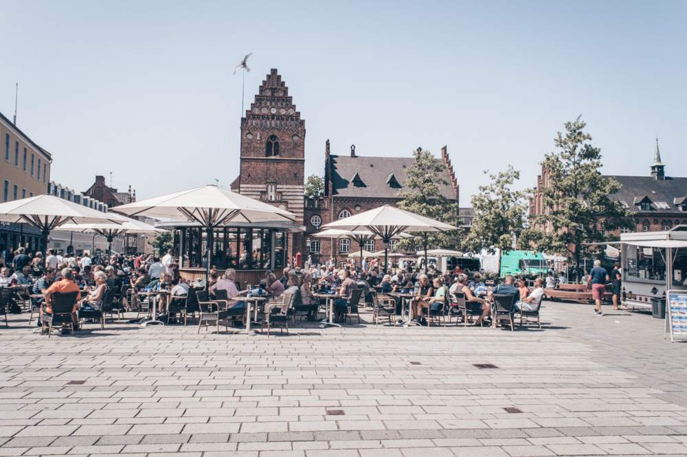 Day Trips from Copenhagen: People in the main square of Roskilde with City Hall in the background