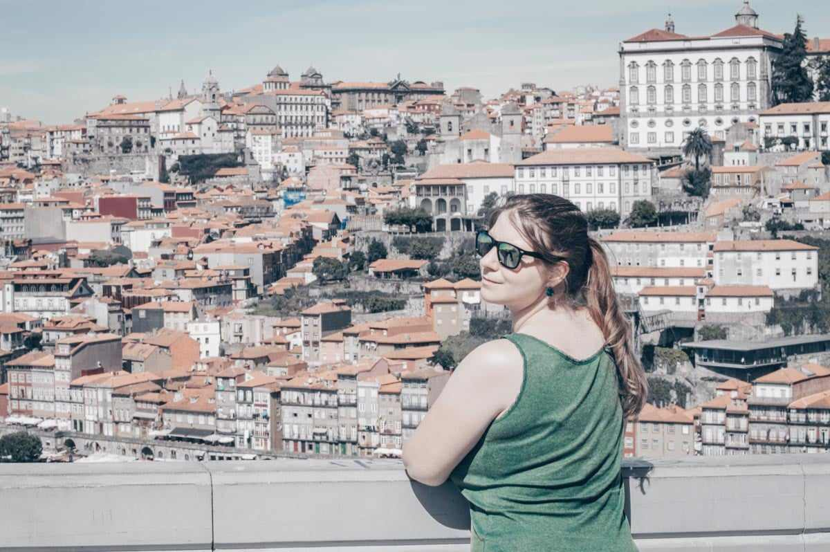 Things to see in Porto: Beautiful woman looking at the camera with the picturesque Ribeira in the background