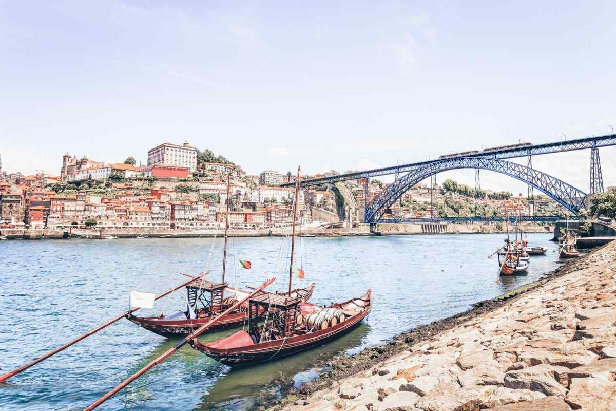 24 Hours in Porto: Picturesque Rabelo boats on the Douro River with the Ribeira and Dom Luis Bridge in background.