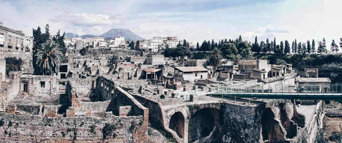Visit Herculaneum: Ruins of the ancient city of Herculaneum with Mt. Vesuvius in the background.