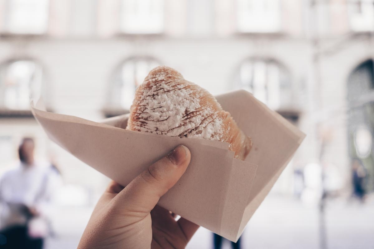 Italian pastries: Woman holding a sfogliatella, a shell-shaped, cheese-filled Italian pastry.