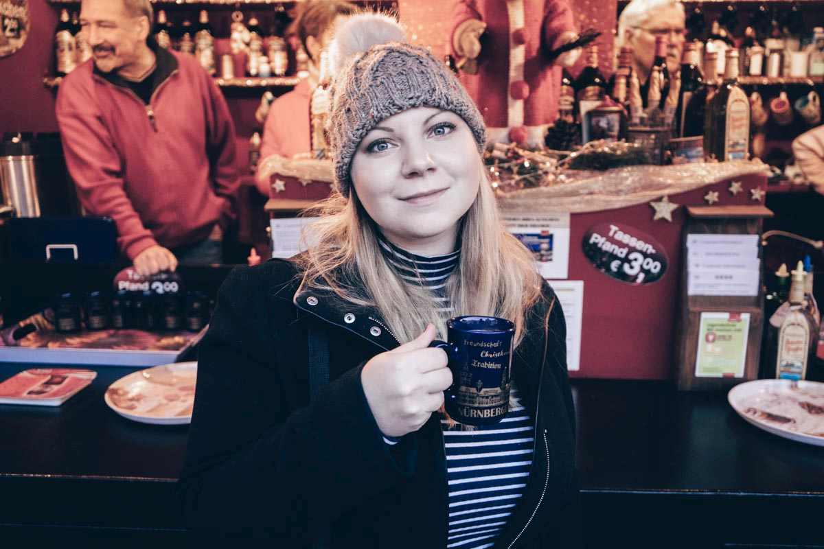 Nuremberg Christmas Market: Beautiful woman drinking  a cup of spicy mulled wine