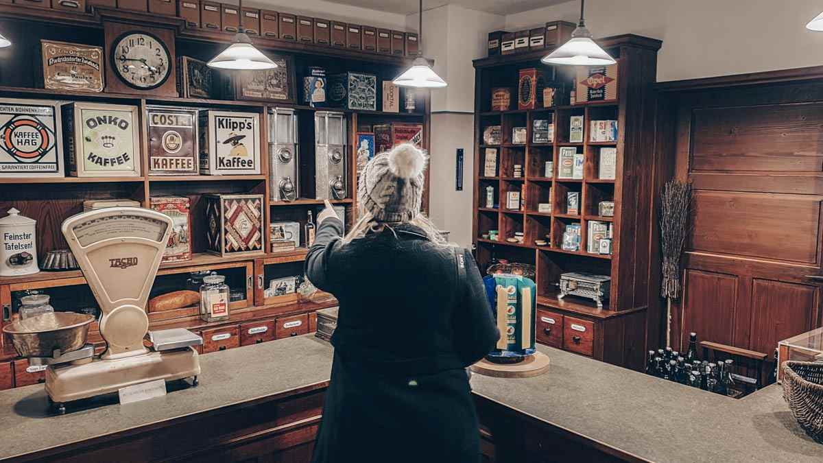 Museum of Industrial Culture Nuremberg: Woman pointing at items inside a reproduction of a vintage shop.