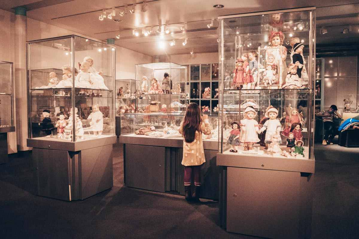Things to see in Nuremberg: A young girl observing the doll collection at the Toy Museum
