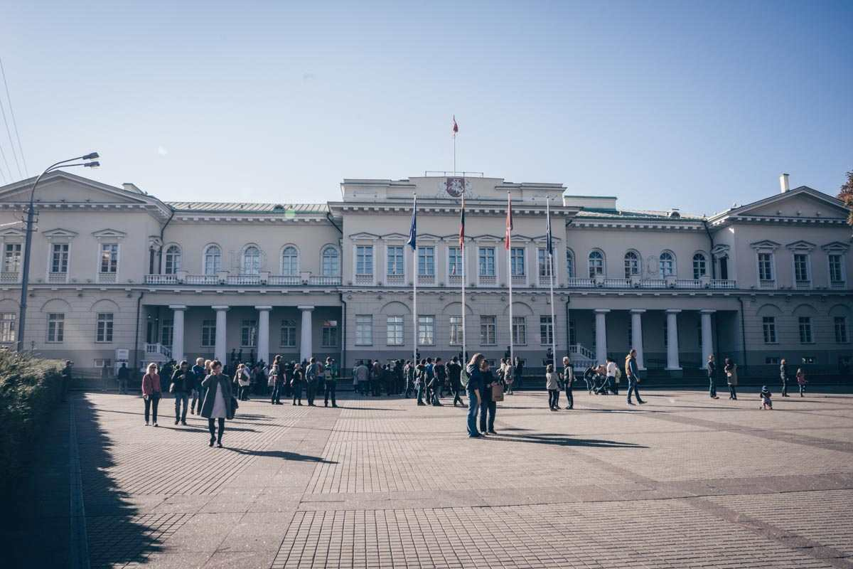 Vilnius must-see sights: People standing outside the cream-colored Presidential Palace