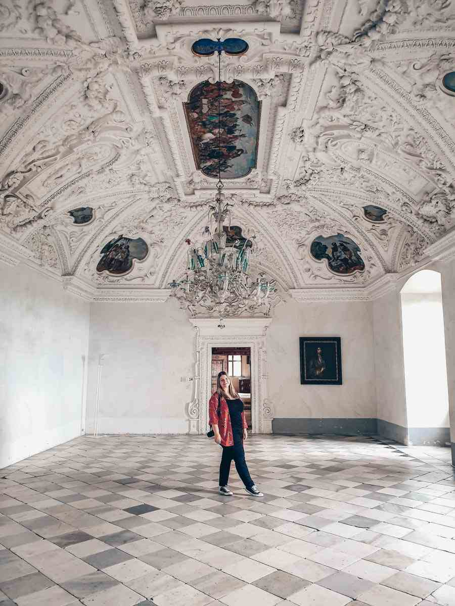 Riegersburg Castle: Beautiful woman inside the White Dining Room, which features lovely stucco work and ceiling paintings