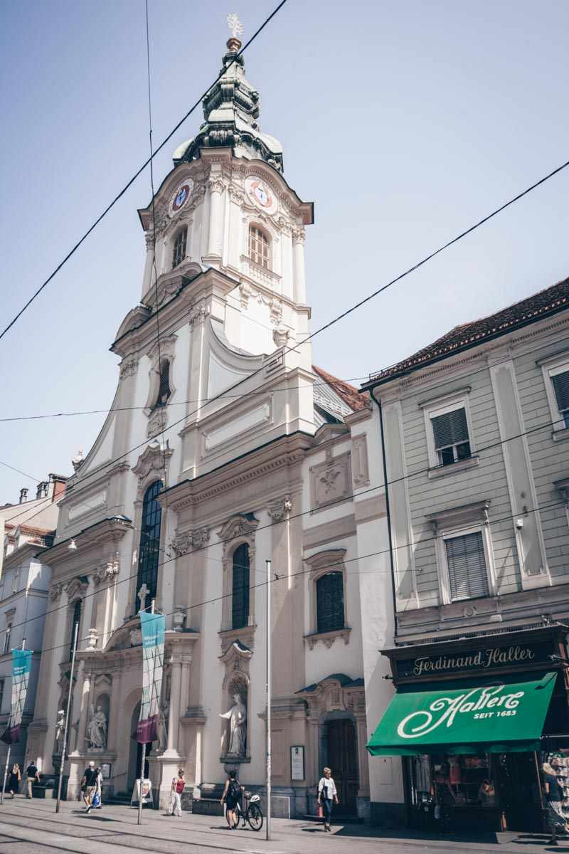 Places to see in Graz: Attractive facade and Baroque spire of the City Parish Church