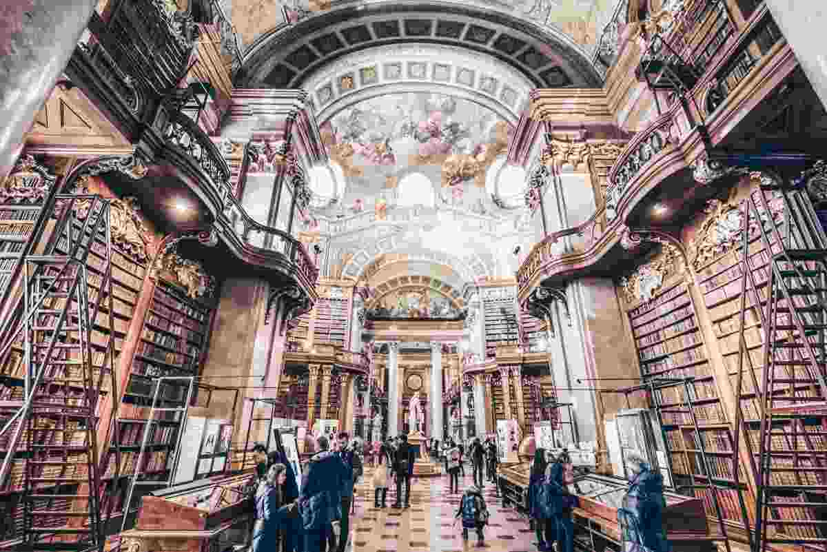 People admiring the manuscripts and ornate Baroque interior of the Austrian National Library. PC: aliaksei kruhlenia/shutterstock.com
