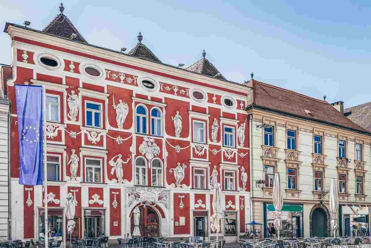 Leoben: Glittering red facade of the Baroque Hacklhaus, with stucco adornments