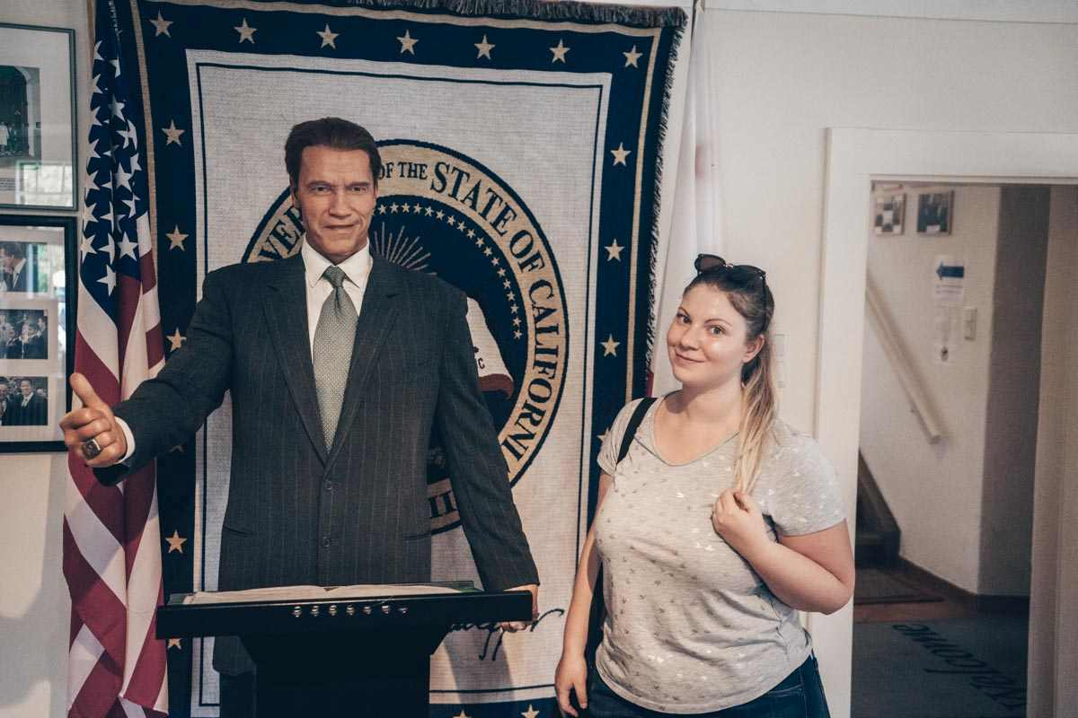 Day Trips from Graz: A beautiful woman standing beside a wax figure of Arnie at the Schwarzenegger Museum