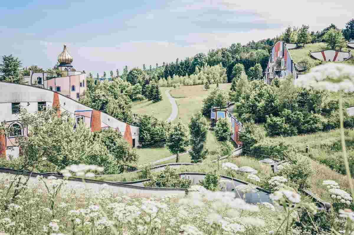 Bad Blumau: View of the colorful buildings set amidst lush green meadows of the Styrian countryside