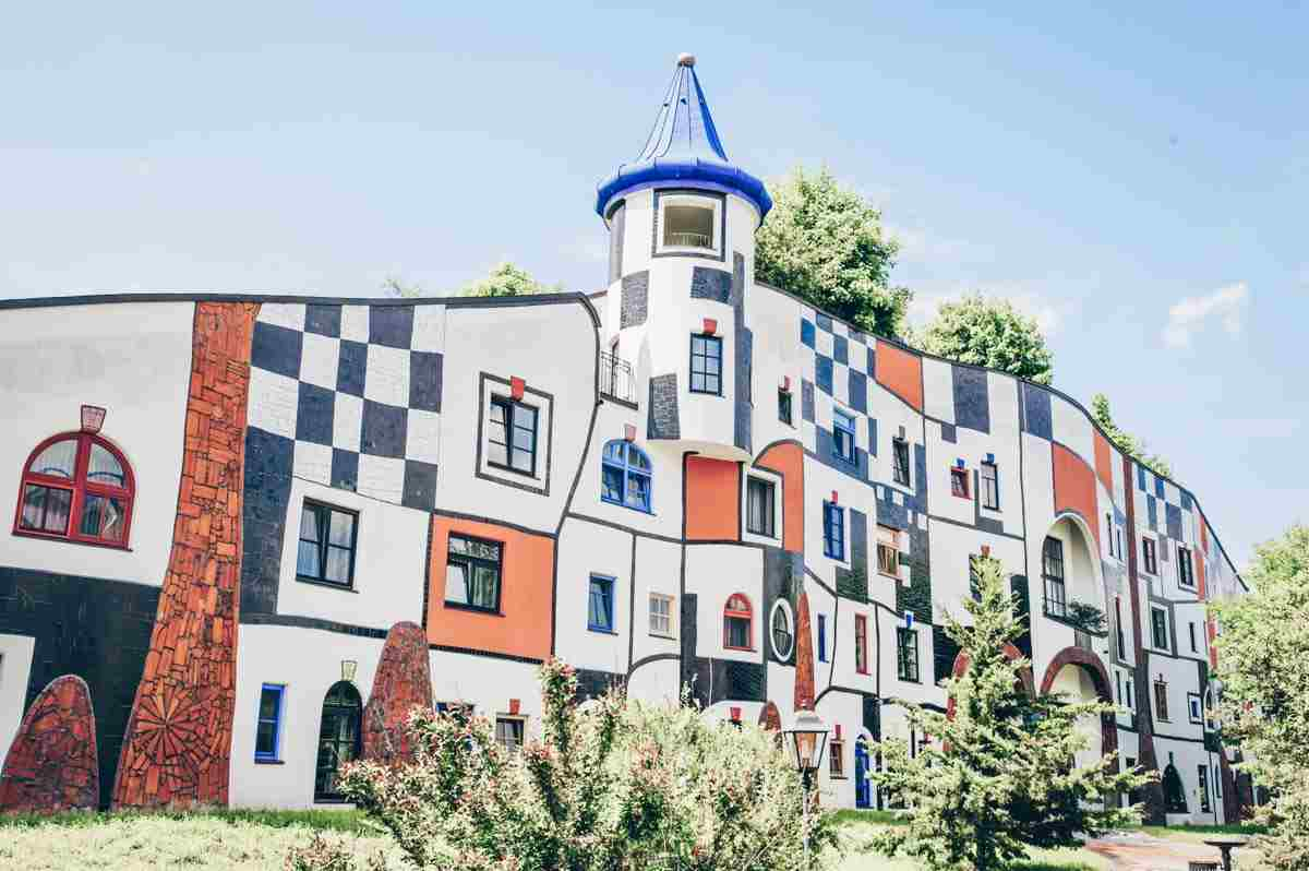 Bad Blumau: A rainbow colored facade of a building at the spa designed by Hundertwasser
