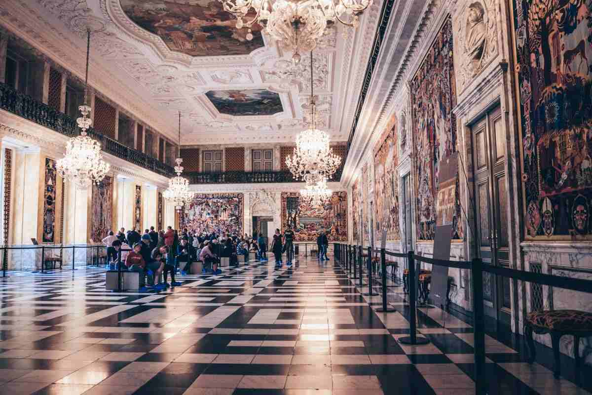 People admiring the colorful wall tapestries in the Great Hall of Christiansborg Palace