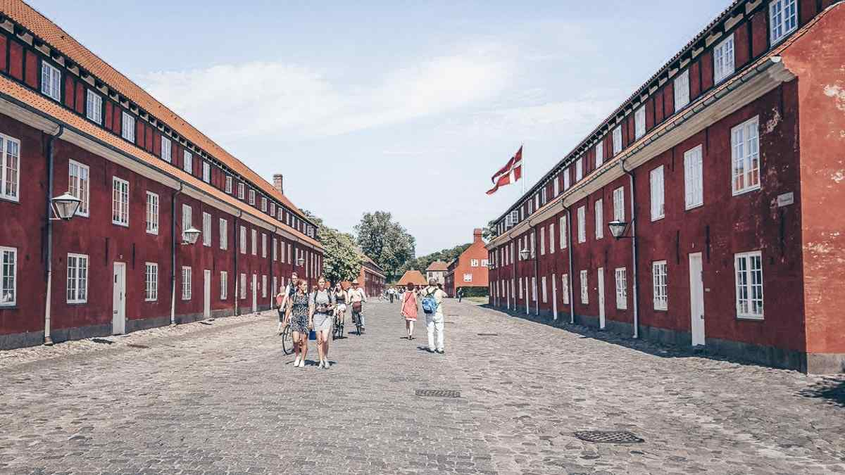 Things to do in Copenhagen: People walking among the red army barracks of Kastellet